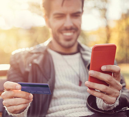 Man holding up debit card and looking at his mobile device