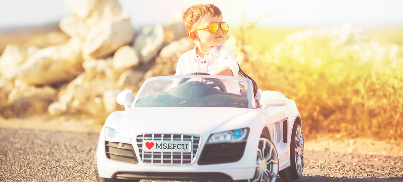 A little boy driving a white ride on toy car.