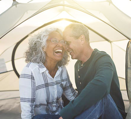 laughing mature couple in camping tent