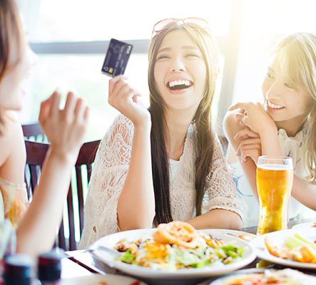 girls laughing at meal while one holds card to pay
